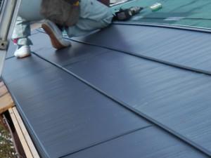 練馬区 屋根カバー工法 既存のスレート屋根の上に金属屋根の横暖ルーフきわみを施工スタッフで葺いていく