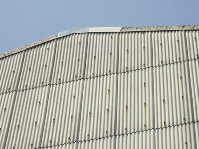 ケラバを板金で補修した大波スレートの倉庫
